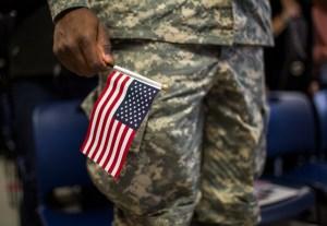 Soldado sostiene bandera de EEUU durante ceremonia de naturalización en NY