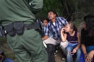 Agente de partulla fronteriza habla con inmigrante con hijos